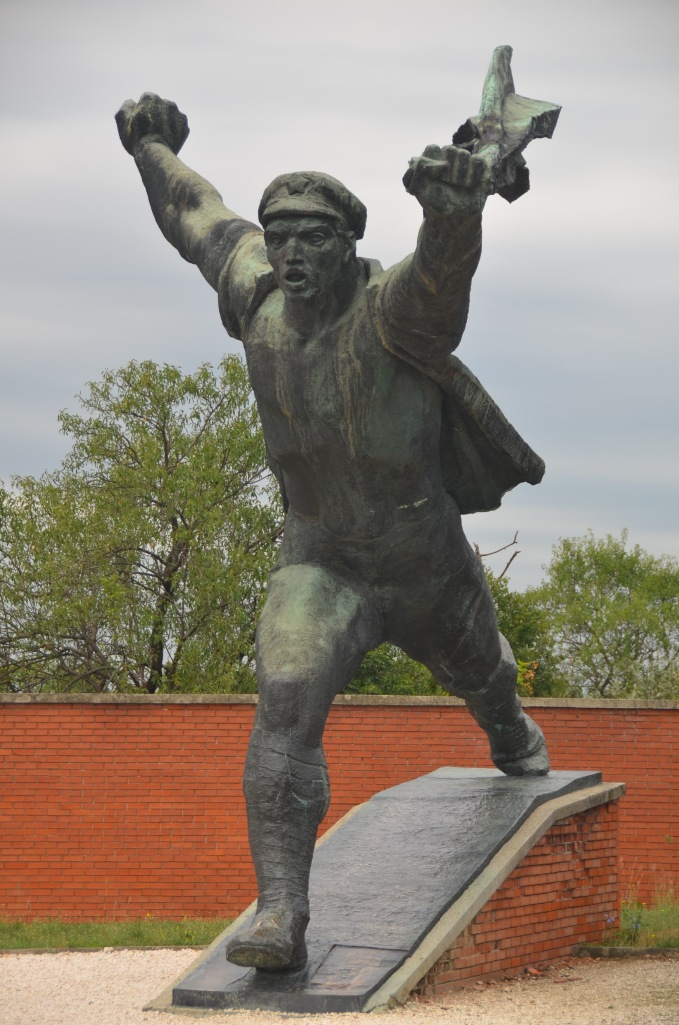 Notice the strong figure, the determined stance, and forward stride typical of a Soviet Realist depiction of an obedient and enthusiastic Soviet worker.
